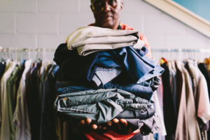 man holding stack of clothes