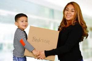Woman and Child moving belongings into new housing