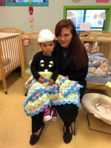 Homeless mother and child at Atlanta Mission with donated blanket and hat