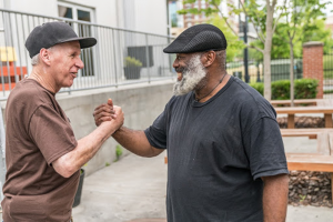 two men shaking hands help those facing homelessness feel empowered