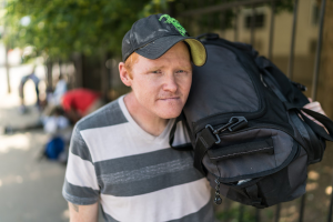 man carrying bag facing homelessness in the summer