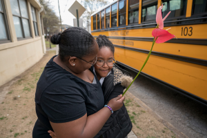 mom and daughter in front of bus - educational challenges for children facing homelessness