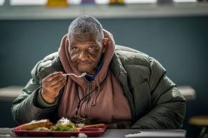 person eating food during Thanksgiving at Atlanta Mission