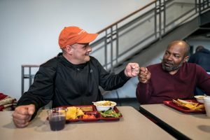 Two men sharing a meal at Atlanta Mission showing the power of intentional relationships