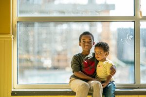 two children facing homelessness sitting in a window