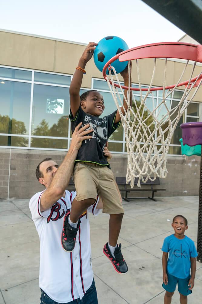 children facing homelessness playing basketball at Atlanta Mission
