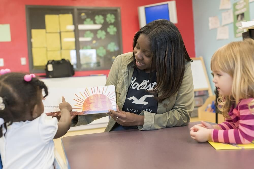 woman reading to children facing homelessness at Atlanta Mission